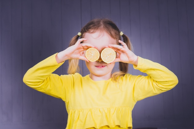 Menina bonita sorridente em camisas amarelas, segurando metades de frutas frescas de limão azedo perto dos olhos e sobre fundo cinza de madeira.