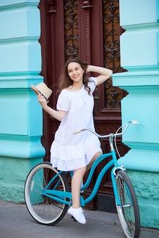 Menina bonita sorridente em vestido branco, montando a bicicleta azul vintage perto do belo edifício azul antigo com portas vermelhas antigas