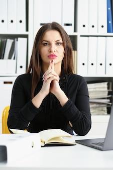 Menina bonita sorridente funcionário no local de trabalho falar com o visitante