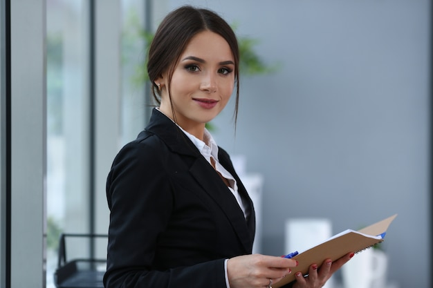 Menina bonita sorridente funcionário vestindo terno segurar notebook