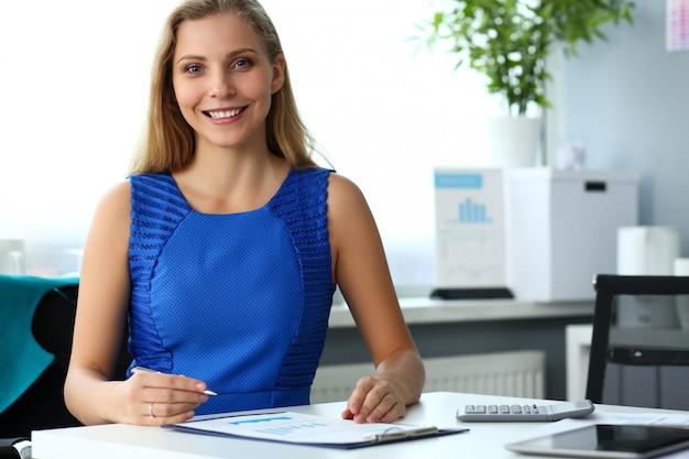 Menina bonita sorridente funcionário vestindo vestido azul