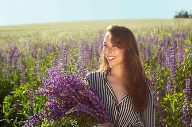 Menina bonita sorridente posando com uma braçada de tremoço no campo de tremoço