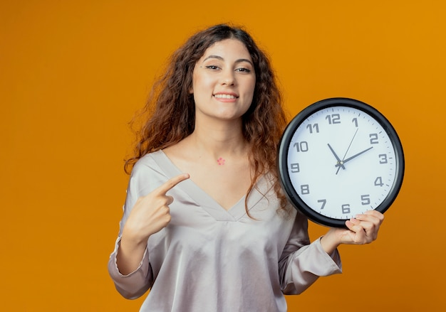Menina bonita sorridente segurando e apontando para o relógio de parede isolado na parede amarela