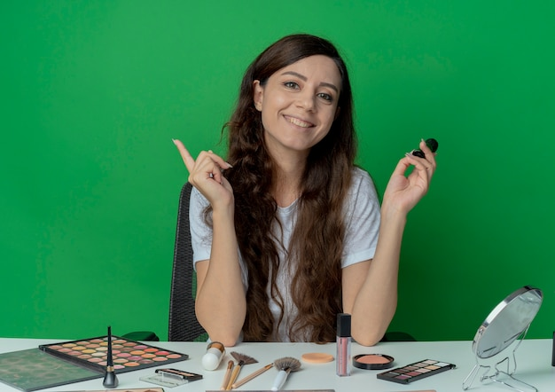 Menina bonita sorridente sentada à mesa de maquiagem com ferramentas de maquiagem segurando o pincel de maquiagem e levantando o dedo isolado sobre fundo verde