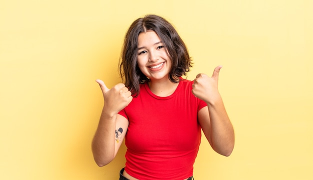 Menina bonita sorrindo alegremente e parecendo feliz, sentindo-se despreocupada e positiva com os dois polegares para cima
