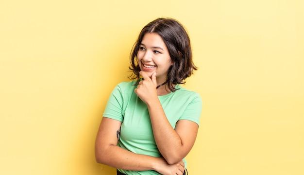 Menina bonita sorrindo com uma expressão feliz e confiante com a mão no queixo, pensando e olhando para o lado