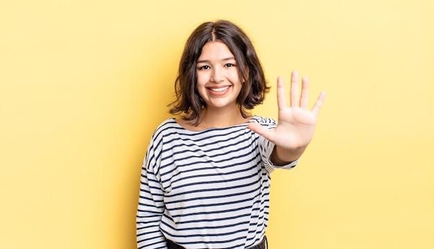Menina bonita sorrindo e parecendo amigável, mostrando o número cinco ou quinto com a mão para a frente, em contagem regressiva