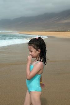 Menina bonita sorrindo enquanto estiver jogando na praia