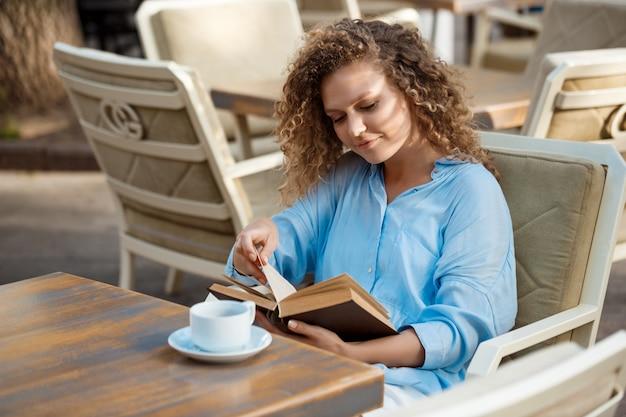 Menina bonita sorrindo, lendo o livro, sentado no café.