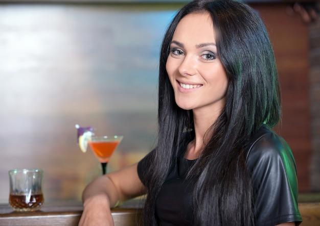 Menina bonita sorrindo para a câmera no bar.