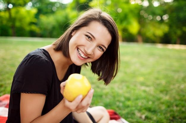Menina bonita sorrindo, segurando a maçã no piquenique no parque.