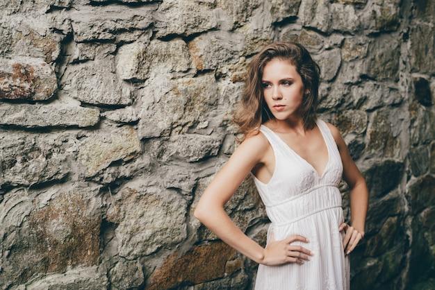 Menina bonita sozinha com cabelos naturais encaracolados em vestido branco no antigo túnel perto da parede musgosa pedregosa.