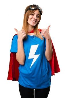 Menina bonita super-herói com o polegar para cima