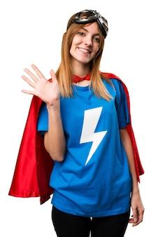 Menina bonita super-herói saudando