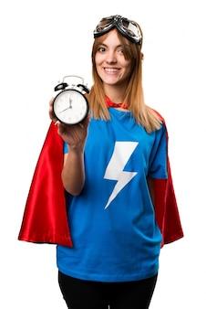 Menina bonita super-herói segurando o relógio vintage