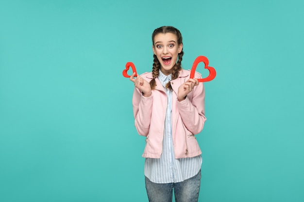 Menina bonita surpresa em estilo casual, penteado pigtail e jaqueta rosa, em pé e segurando formas de coração vermelho e olhando para a câmera com rosto surpreso, interior, isolado em fundo azul ou verde