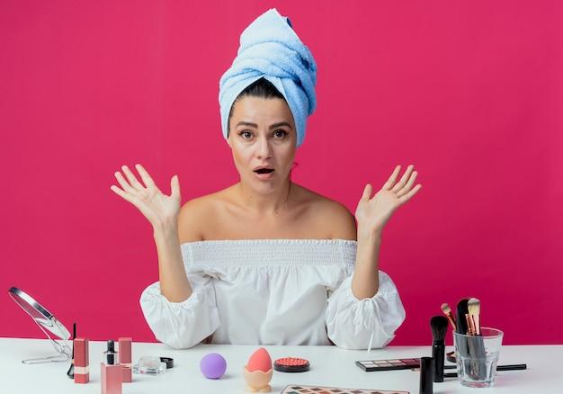 Menina bonita surpresa enrolada em toalha de cabelo se senta à mesa com ferramentas de maquiagem e levanta as mãos isoladas na parede rosa