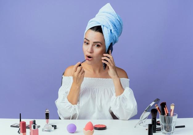 Menina bonita surpresa enrolada em toalha de cabelo se senta à mesa com ferramentas de maquiagem segurando e aplicando brilho labial falando no telefone isolado na parede roxa