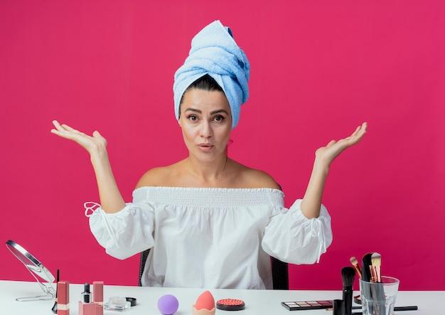 Menina bonita surpresa, enrolada em toalha de cabelo, senta-se à mesa com ferramentas de maquiagem e levanta as mãos isoladas na parede rosa