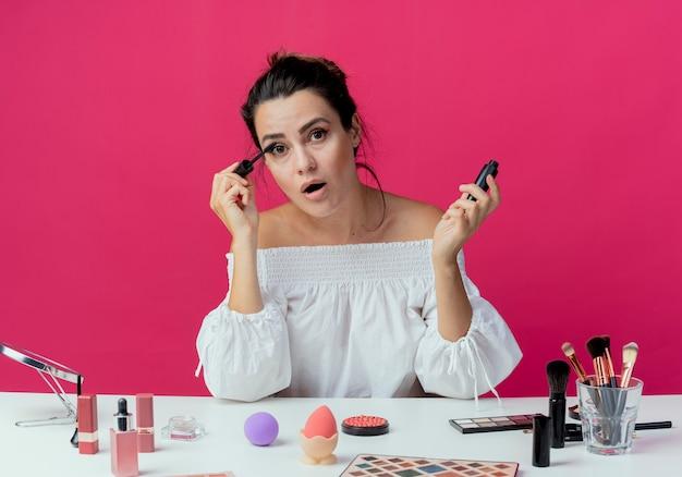 Menina bonita surpresa sentada à mesa com ferramentas de maquiagem aplicando rímel e parecendo isolado na parede rosa