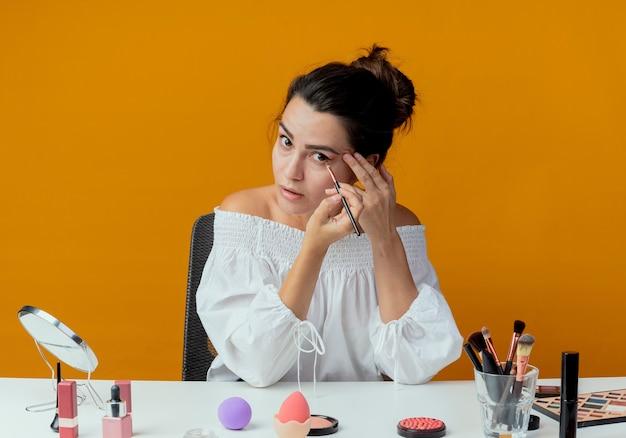 Menina bonita surpresa sentada à mesa com ferramentas de maquiagem, aplicando sombra com pincel de maquiagem, parecendo isolada na parede laranja