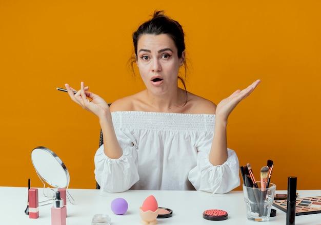 Menina bonita surpresa sentada à mesa com ferramentas de maquiagem, levantando as mãos e segurando o delineador isolado na parede laranja