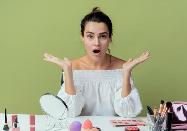 Menina bonita surpresa sentada à mesa com ferramentas de maquiagem, levantando as mãos isoladas na parede verde