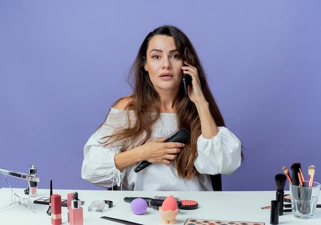 Menina bonita surpresa sentada à mesa com ferramentas de maquiagem segurando pente de cabelo falando no telefone isolado na parede roxa