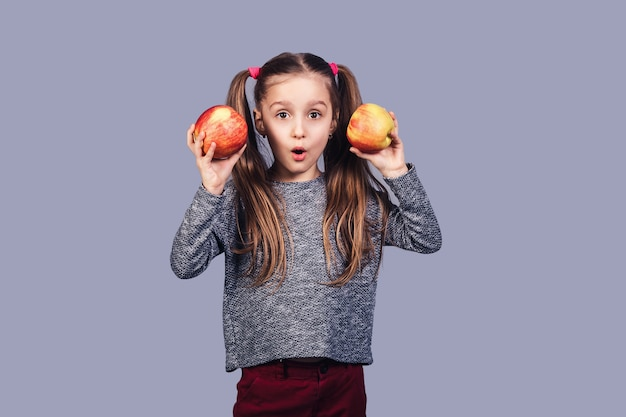 Menina bonita tem duas maçãs nas mãos e mostra uma cara de surpresa. isolado na superfície cinza