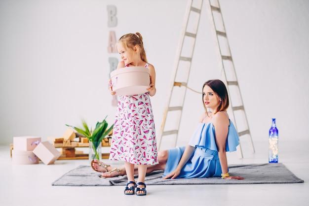 Menina bonita tem um presente para o pai nas mãos dela e espere por ele. mãe adorável com a filha no quarto decorado branco.