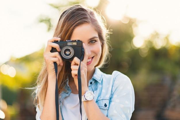 Menina bonita tirando fotos com uma câmera vintage em um dia ensolarado
