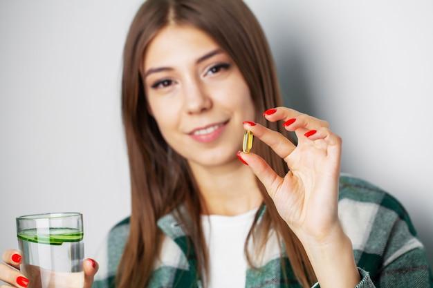 Menina bonita toma um comprimido para perda de peso
