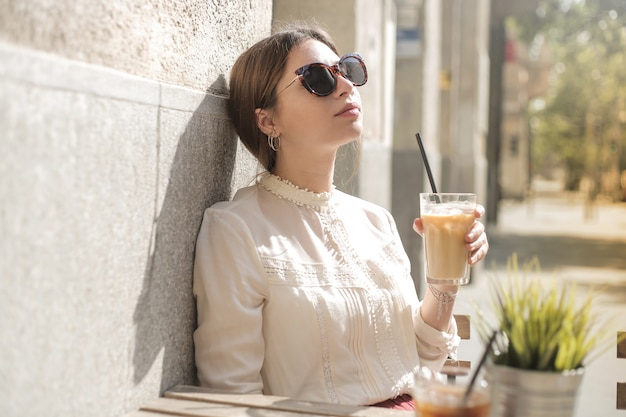 Menina bonita tomando um café gelado