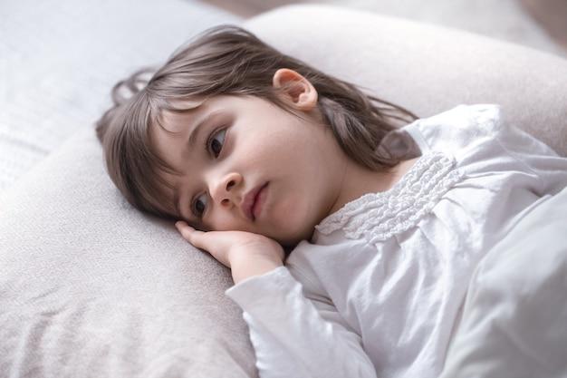Menina bonita triste na cama, conceito de sono