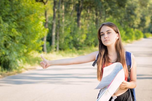 Menina bonita turista levanta a mão e pára um carro no campo para pedir uma maneira