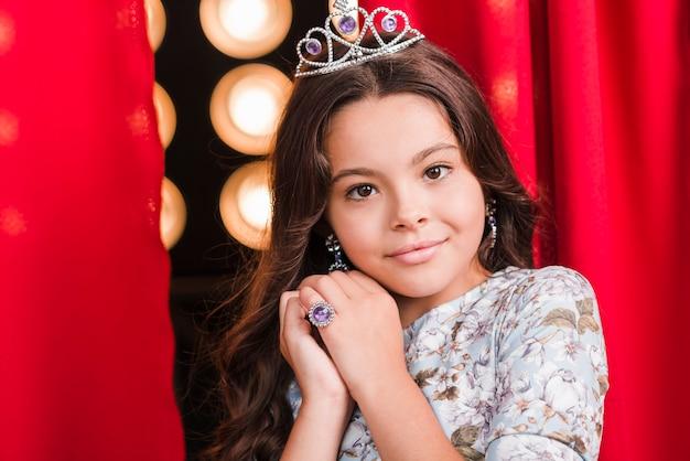 Menina bonita usando coroa em pé na frente da cortina vermelha