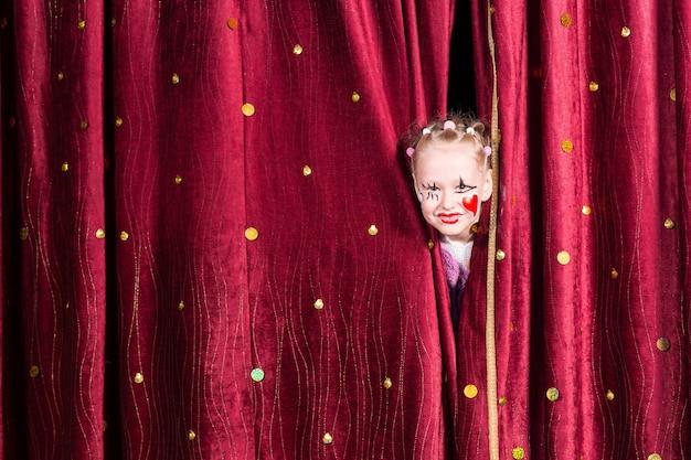 Menina bonita usando maquiagem colorida com um coração vermelho na bochecha espiando por entre as cortinas esperando para entrar no palco durante uma pantomima