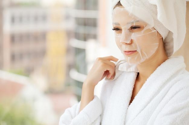 Menina bonita usando máscara facial em casa.
