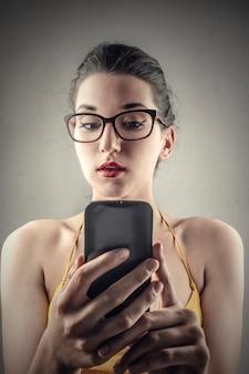 Menina bonita usando um aplicativo em seu telefone
