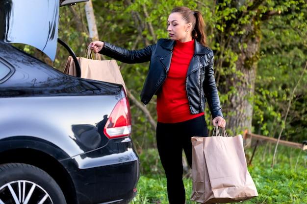 Menina bonita vestida casualmente coloca sacos de papel na mala do carro na natural