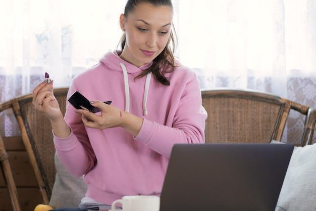 Menina bonita, vestida com capuz rosa, fazendo maquiagem, olhando para o computador portátil