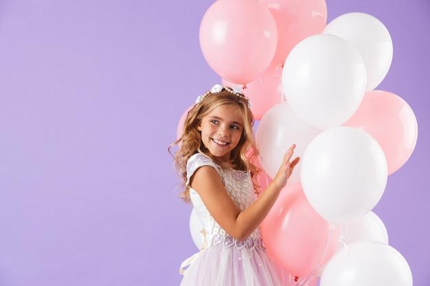 Menina bonita vestida com vestido de princesa isolado sobre a parede violeta, segurando um monte de balões