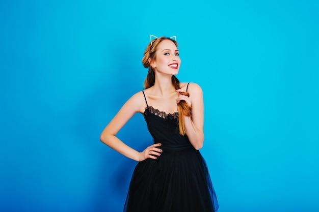 Menina bonita vestida para festa, sorrindo e posando. usando um vestido preto elegante e tiara de orelha de gato com diamantes, bela maquiagem e manicure dourada.
