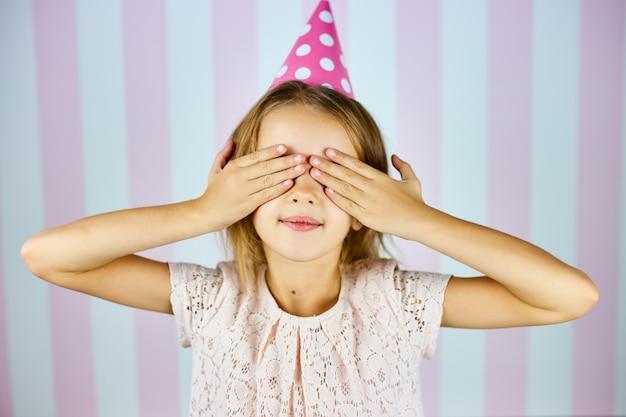 Menina bonita vestindo boné rosa aniversário, esperando a surpresa, fechar os olhos, sorrindo com sorriso no rosto. feliz aniversário.