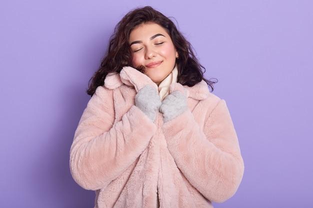 Menina bonita vestindo casaco de pele sintética rosa pálido