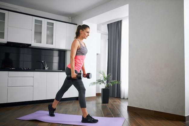 Menina bonita vestindo roupa esportiva, treinamento e respiração em casa pela manhã, usando halteres.