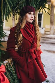 Menina bonita, vestindo um casaco vermelho e uma boina na rua de natal