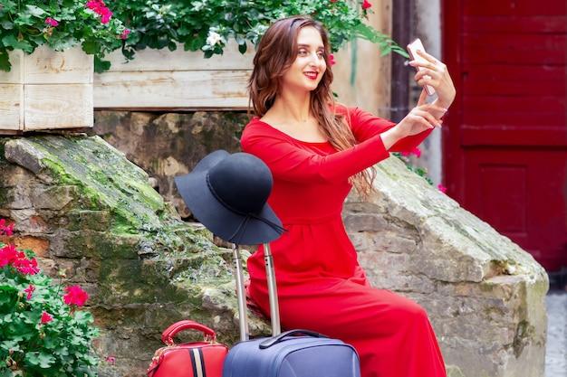Menina bonita viajante está tomando selfie ao ar livre