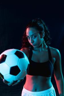 Menina bonita vista frontal, segurando uma bola de futebol