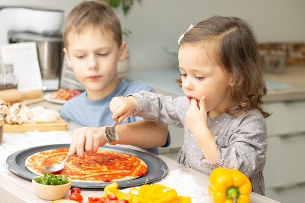 Menina bonitinha 2-4 em vestido cinza e menino 7-10 em t-shirt cozinhando pizza juntos na cozinha. irmão e irmã cozinhando